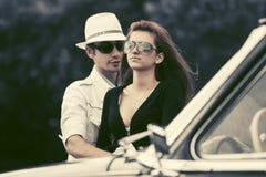 Szczęśliwa potomstwo mody para obok rocznika samochodu obraz royalty free