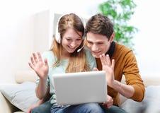 Szczęśliwa potomstwo para opowiada przez komputeru z wideo gadką zdjęcia royalty free