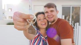 Szczęśliwa potomstwo para stoi outdoors trzymać kluczowy ich nowy dom zbiory wideo