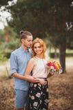 Szczęśliwa potomstwo para wydaje czas plenerowego w jesień parku Facet dać kwiaty piękna dziewczyna z czerwonym włosy zdjęcia royalty free
