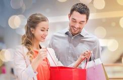 Szczęśliwa potomstwo para z torba na zakupy w centrum handlowym Fotografia Stock