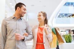 Szczęśliwa potomstwo para z torba na zakupy w centrum handlowym Fotografia Royalty Free
