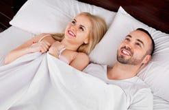 Szczęśliwa pozytywna para pozuje w rodzinnym łóżku Obrazy Stock