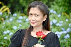 Szczęśliwa Przechodzić na emeryturę Różnorodna Żeńska Starsza kobieta Z kwiatem obrazy stock