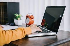 Szczęśliwa przypadkowa młoda azjatykcia kobieta pracuje w domowym, małym biurze z używać lub donosi na biurku jako freelancer obraz stock