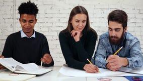 Szczęśliwa różnorodna grupa ucznie lub młoda biznes drużyna pracuje na projekcie Młody afrykański facet pokazuje rezultaty zbiory wideo