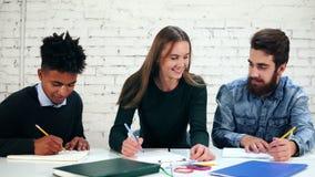 Szczęśliwa różnorodna grupa ucznie lub młoda biznes drużyna pracuje na projekcie Młodzi ucznie przygotowywa ich pracę domową zbiory wideo