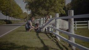 Szczęśliwa różnorodna rodzina z dzieciakami muska konia w gospodarstwie rolnym zdjęcie wideo