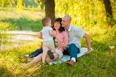 Szczęśliwa radosna młoda rodzina z dzieckiem outdoors Fotografia Stock
