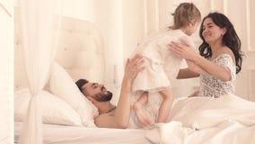 Szczęśliwa rodzina ściska each inny w łóżku na pogodnym ranku zbiory wideo