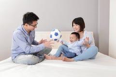 Szczęśliwa rodzina bawić się zabawkarską piłkę nożną obraz stock