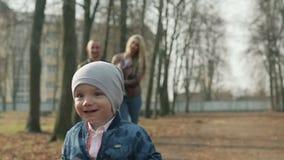 Szczęśliwa rodzina chodzi w wiosna parku trzy zbiory
