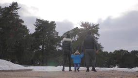 Szczęśliwa rodzina chodzi w zimy lasowym rodzicielstwie, sezonie i ludziach pojęć, zbiory