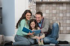 Szczęśliwa rodzina czytająca wpólnie Obrazy Royalty Free