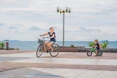 Szczęśliwa rodzina jest jeździeckimi rowerami i ono uśmiecha się outdoors Mama na rowerze Zdjęcia Royalty Free