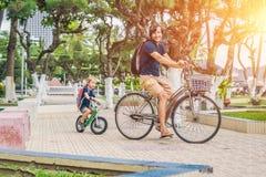 Szczęśliwa rodzina jest jeździeckimi rowerami i ono uśmiecha się outdoors Ojciec na b Fotografia Royalty Free