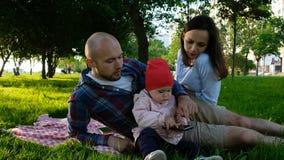 Szczęśliwa rodzina jest odpoczynkowa w parku na trawie Młode dziecko trzyma smartphone w rękach zdjęcia stock