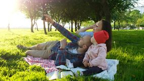 Szczęśliwa rodzina kłaść na pled i robi selfie z dzieckiem przy zmierzchem w parku Ojciec bierze obrazki zdjęcie stock