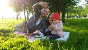Szczęśliwa rodzina kłaść na trawie robi selfie z dzieckiem przy zmierzchem w parku na smartphone ojcu i zdjęcia royalty free