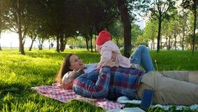 Szczęśliwa rodzina kłama na sztukach z dzieckiem i trawie przy zmierzchem w parku zdjęcie stock