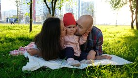 Szczęśliwa rodzina kłama na trawie w lato parku Rodzice całują troszkę dziewczynki na policzkach na obich stronach zdjęcie stock