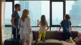 Szczęśliwa rodzina, kobieta, mężczyzna i dwa dziecka z walizką na tle drapacz chmur w panoramicznym okno, zdjęcia stock
