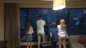 Szczęśliwa rodzina, kobieta, mężczyzna i dwa dziecka z walizką wewnątrz na tle drapacz chmur w panoramicznym okno, zbiory wideo