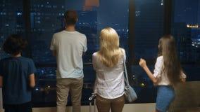 Szczęśliwa rodzina, kobieta, mężczyzna i dwa dziecka z walizką wewnątrz na tle drapacz chmur w panoramicznym okno, zdjęcie wideo