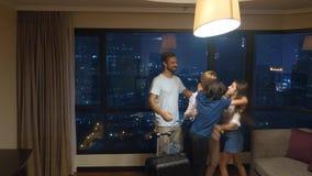 Szczęśliwa rodzina, kobieta, mężczyzna i dwa dziecka z walizką wewnątrz na tle drapacz chmur w panoramicznym okno, zdjęcia stock