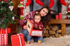 Szczęśliwa rodzina macierzysta i mała córka bawić się w bożych narodzeniach Zdjęcie Royalty Free