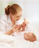 Szczęśliwa rodzina. macierzysty bawić się z jej dzieckiem w łóżku Zdjęcia Royalty Free