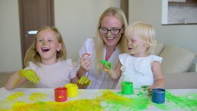 Szczęśliwa rodzina maluje kolory Szczęśliwa rodzina maluje kolory Matka i córka ma zabawę i malujemy each innego ` s na twarzach zbiory