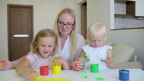 Szczęśliwa rodzina maluje kolory Szczęśliwi mali childs robi kolorowemu koloru handsprint na białym papierze Troszkę śliczny szcz zdjęcie wideo
