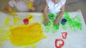 Szczęśliwa rodzina maluje kolory Zakończenie up szczęśliwe małe śliczne dziecka ` s ręki robi farbie kolorowym rysunkom na papier zbiory wideo