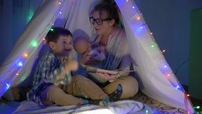 Szczęśliwa rodzina, mama czyta bajki jej synowie siedzi w wigwamu w wieczór zdjęcie wideo