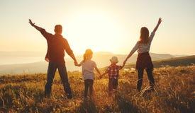 Szczęśliwa rodzina: matka, ojciec, dzieci synowie i córka na zmierzchu, zdjęcie stock
