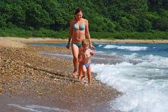 Szczęśliwa rodzina matka z dzieciaka bieg na plaży Fotografia Stock