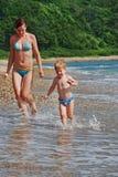 Szczęśliwa rodzina matka z dzieciaka bieg na plaży Zdjęcia Royalty Free
