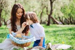 Szczęśliwa rodzina na pinkinie dla matka dnia Mamy i berbecia syna łasowania cukierki plenerowi w wiośnie zdjęcia stock