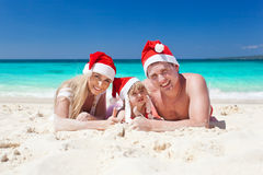 Szczęśliwa rodzina na plaży w Santa kapeluszach, świętowań boże narodzenia Obraz Royalty Free