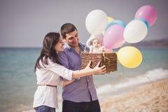 Szczęśliwa rodzina na plaży z ballons i koszem Zdjęcia Royalty Free