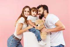 Szczęśliwa rodzina na różowym tle zdjęcia royalty free