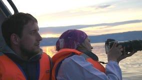 Szczęśliwa rodzina na wakacjach cieszy się łódkowatego przejażdżka puszek podczas zmierzchu jezioro Żeński brunetka podróżnik bie zbiory