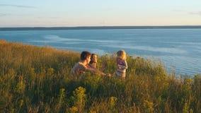 Szczęśliwa rodzina ogląda zmierzch na tle rzeka zdjęcie wideo