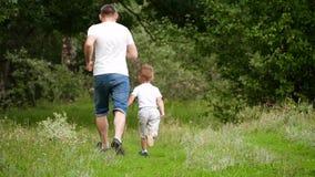 Szczęśliwa rodzina: ojca i syna bieg na zielonej trawie w parku Wiosna i lata plenerowy odtwarzanie zbiory