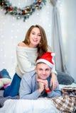 Szczęśliwa rodzina, ojciec i matka w ranku w sypialni dekorował dla bożych narodzeń Ojcuje w Santa kapeluszu kłaść na łóżku i fotografia royalty free
