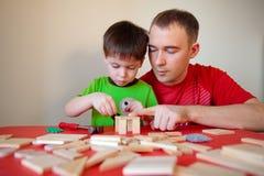 Szczęśliwa rodzina. Ojciec i syn pracuje w domu Obrazy Stock