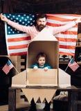 Szczęśliwa rodzina ojciec i syn z usa zaznaczamy rakietę i tapetujemy Zdjęcie Stock