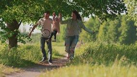 szczęśliwa rodzina Ojcuje, matka i mały powabny córka bieg wzdłuż ścieżki w lasowym parku, trzyma ręki Lato zbiory wideo
