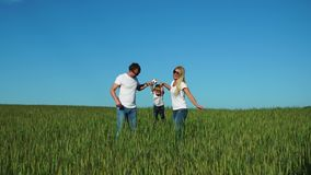 Szczęśliwa rodzina: Ojcuje, matka i syn biega w polu ubierającym w białych koszulkach, zbiory